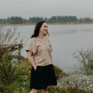 kvinna vid havet som bär beige tshirt och svart kjol i tencel. Zero waste kläder sydda i Finland av Restyle.