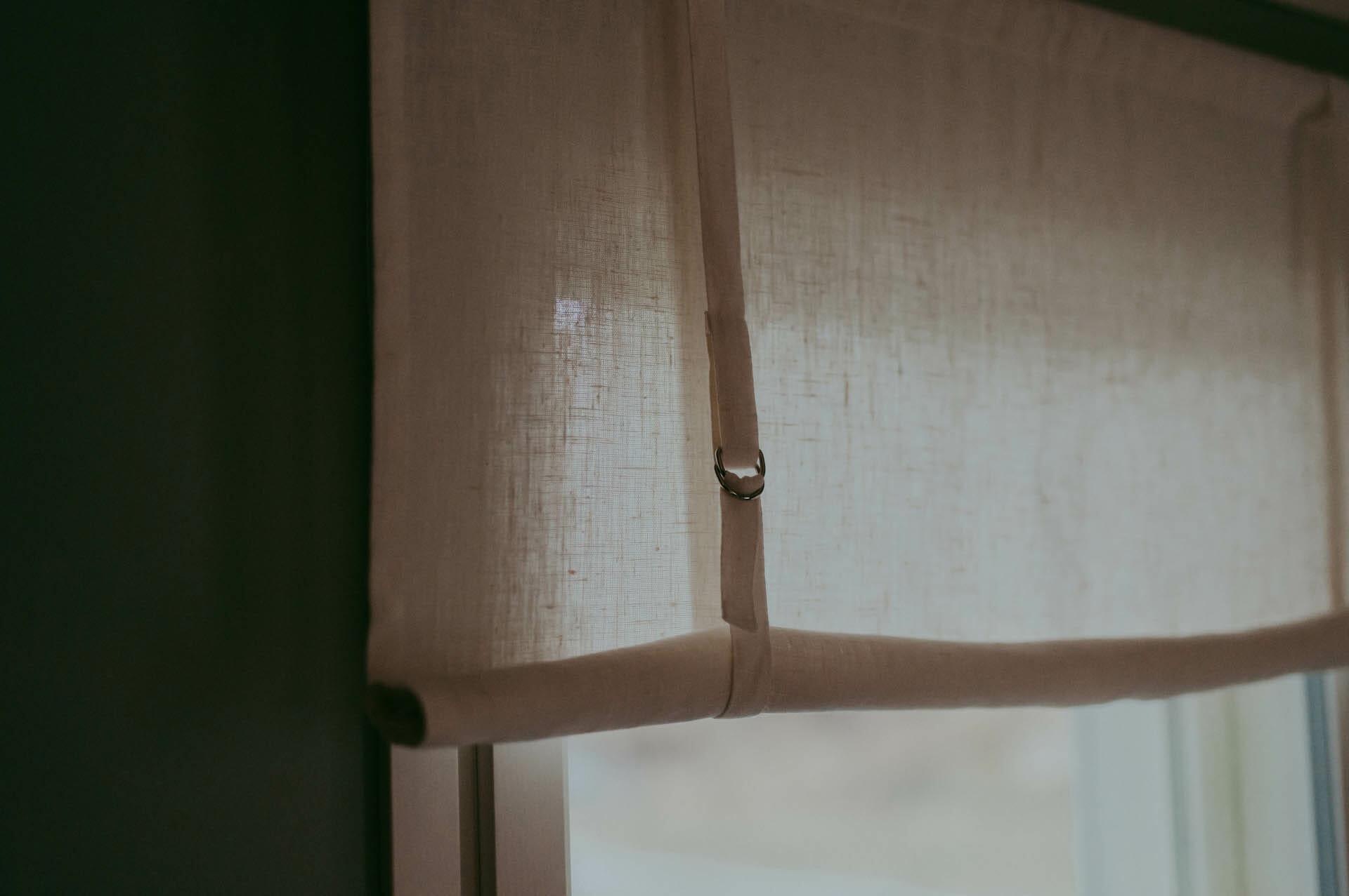 vit rullhissgardin i linne hänger i fönster.