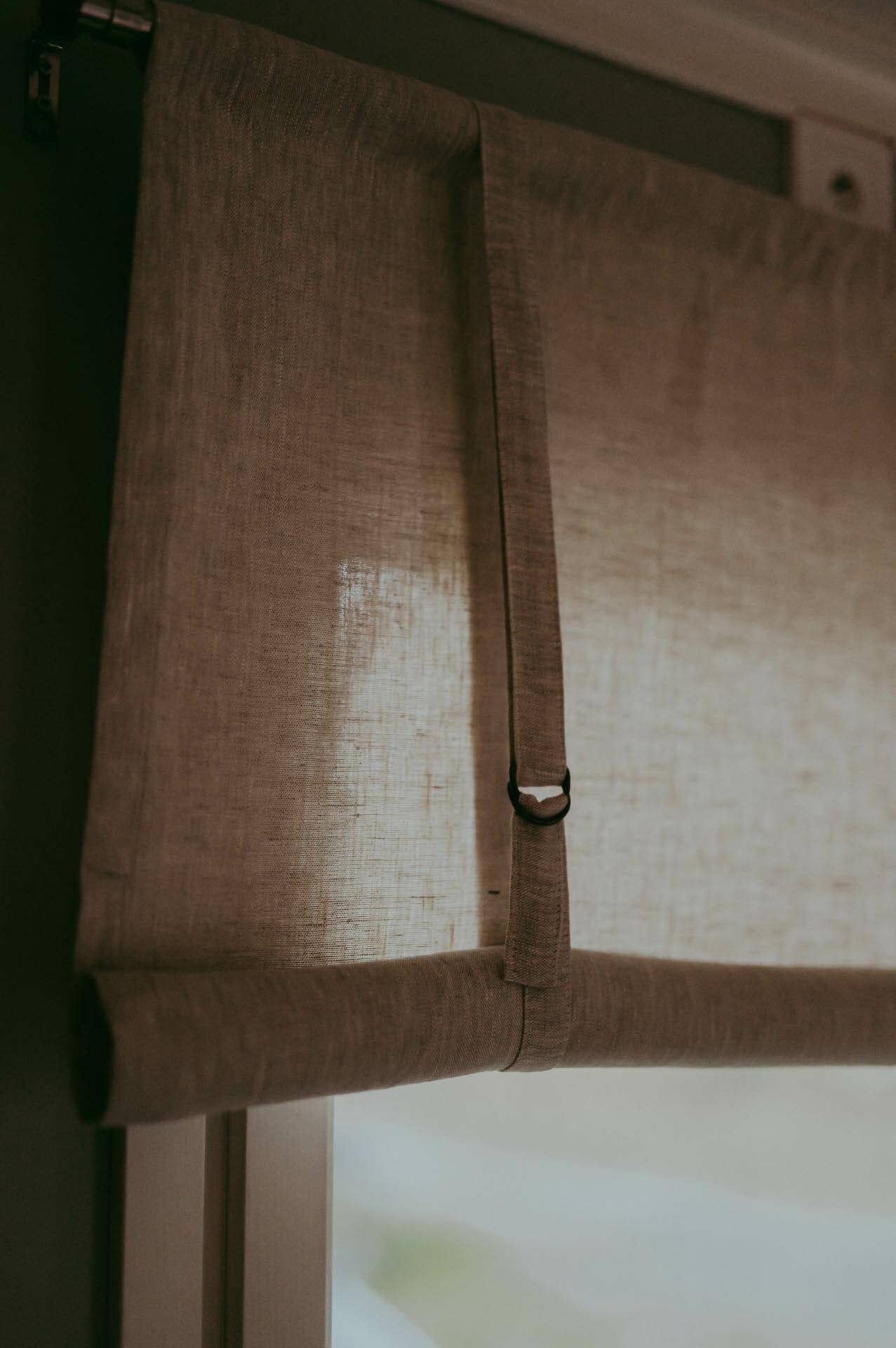 linnefärgad beige rullhissgardin i linne hänger i fönster.