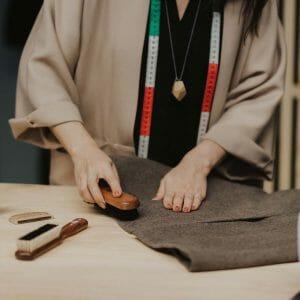 Kvinna visar hur man borstar ylletyg rent med klädborste från KENT brushes.