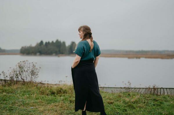 flicka vid havet i blå zero waste tröja och svart kjol.