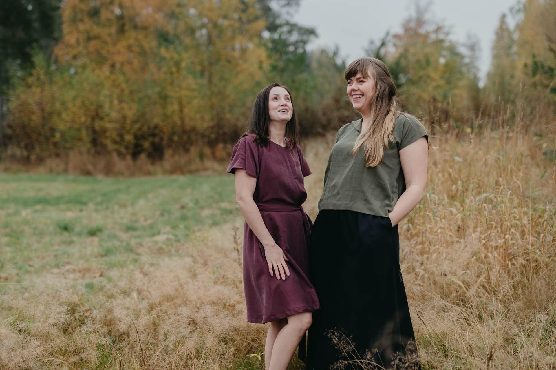 kvinnor på åker i finland i grön top och svart lång kjol som är sydda av RESTYEL syatelje.