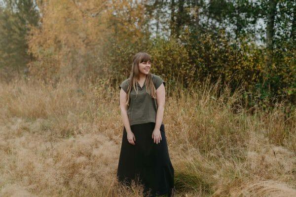 flicka på åker i finland i grön top och svart lång kjol som är sydda av RESTYEL syatelje i Finland.