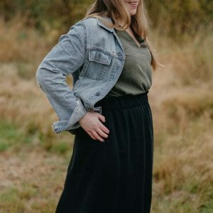 flicka på åker i finland i grön top och svart lång kjol som är sydda av RESTYLE syatelje.