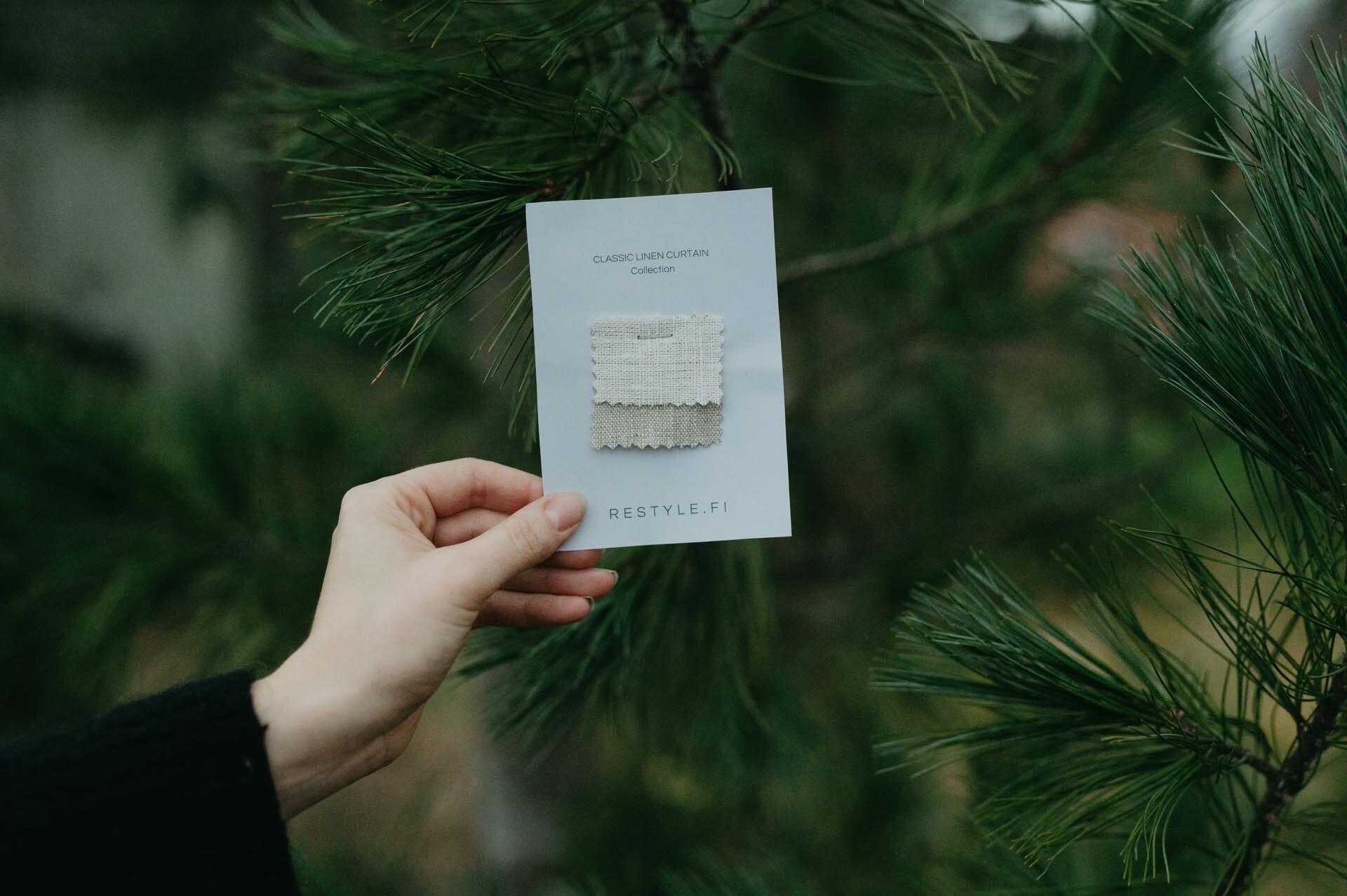 Hand håller i tygprover på linnetyg som kan beställas före köp av gardiner.