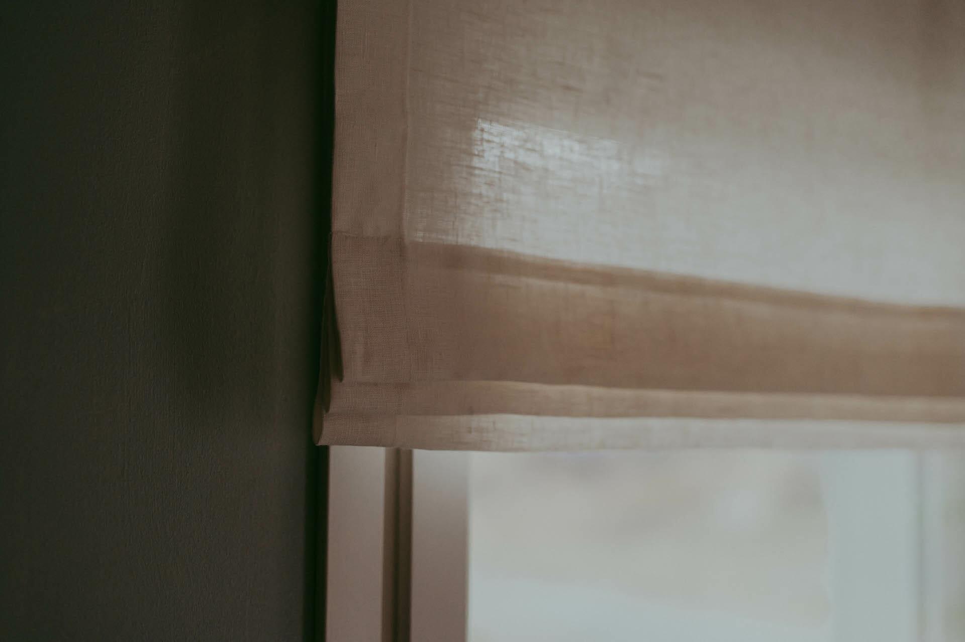 Valkoinen pellava valelaskosverho ikkunassa.