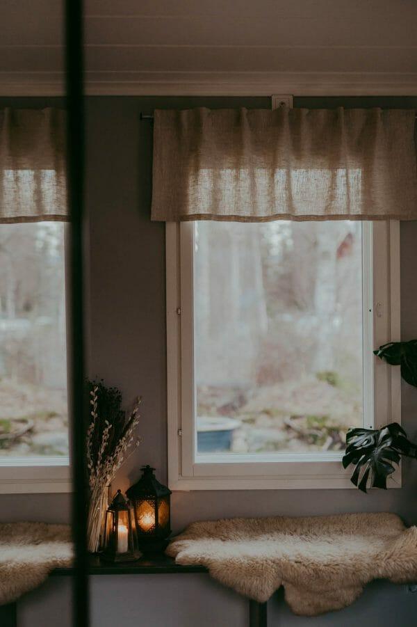 Linnefärgad kappa hänger i mysigt fönster.