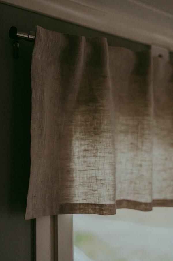 linnefärgad linne gardin kappa i fönster.