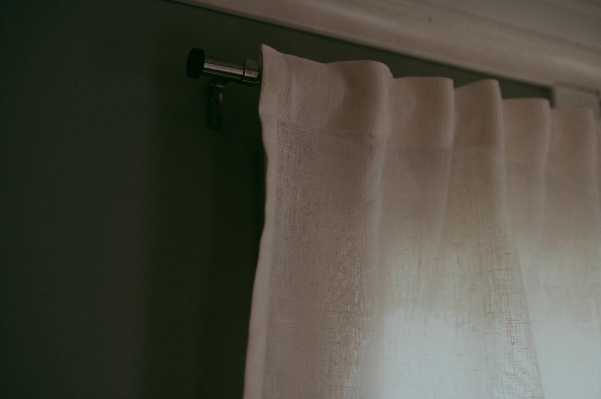 vit linne gardin kappa på gardinsstång.
