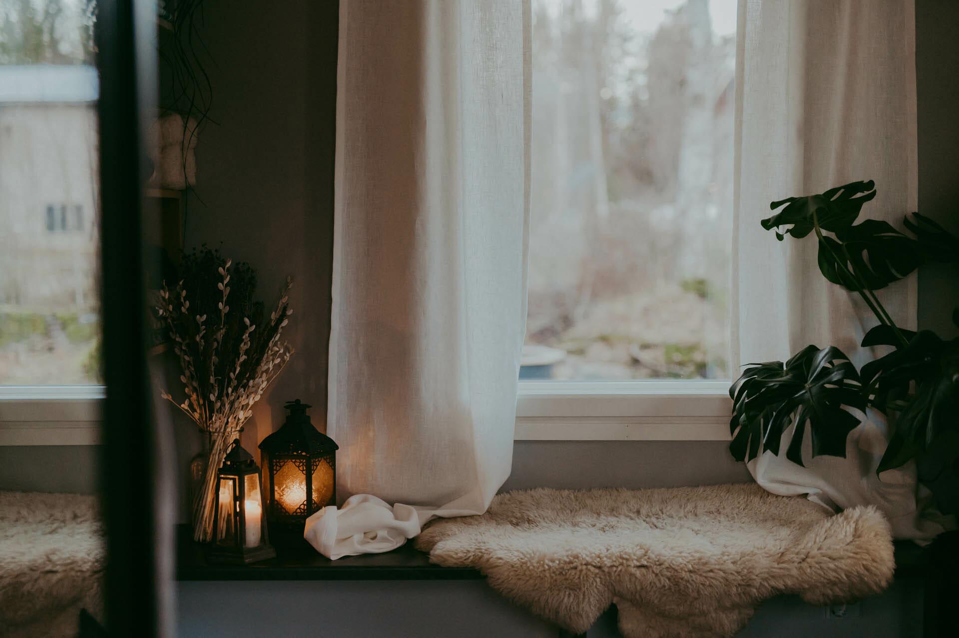 Valkoiset pellavasivuverhot ikkunassa.