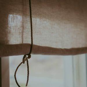 linnefärgad beige rullhissgardin med rep i linne hänger i fönster.
