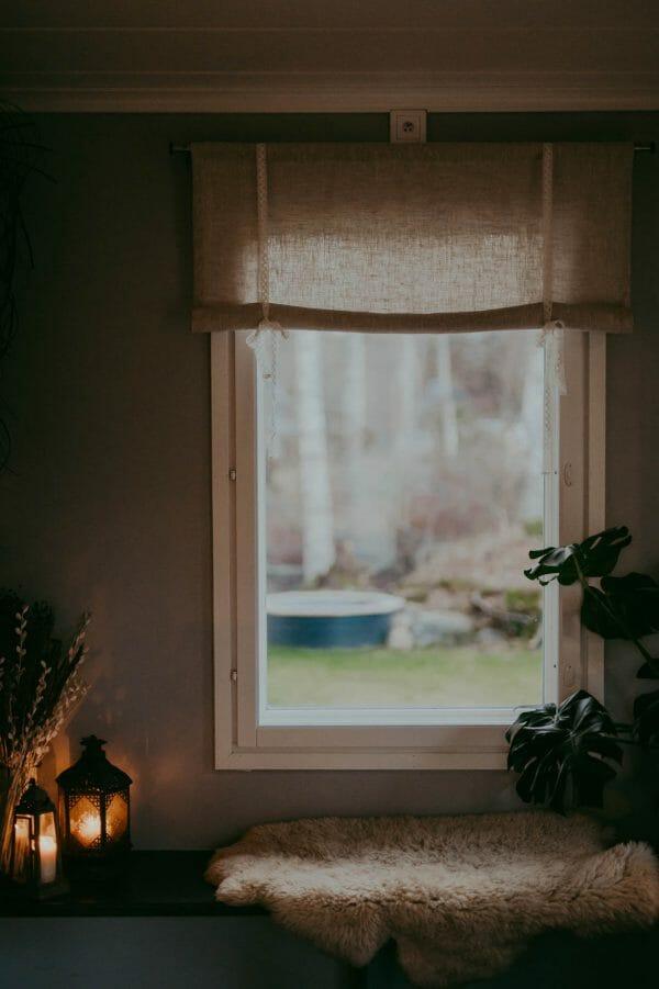 linnefärgad beige rullhissgardin med rep i linne med spetsband rosetter hänger i fönster.