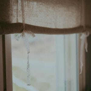Linen roll up curtain hanging in cozy window in finland.