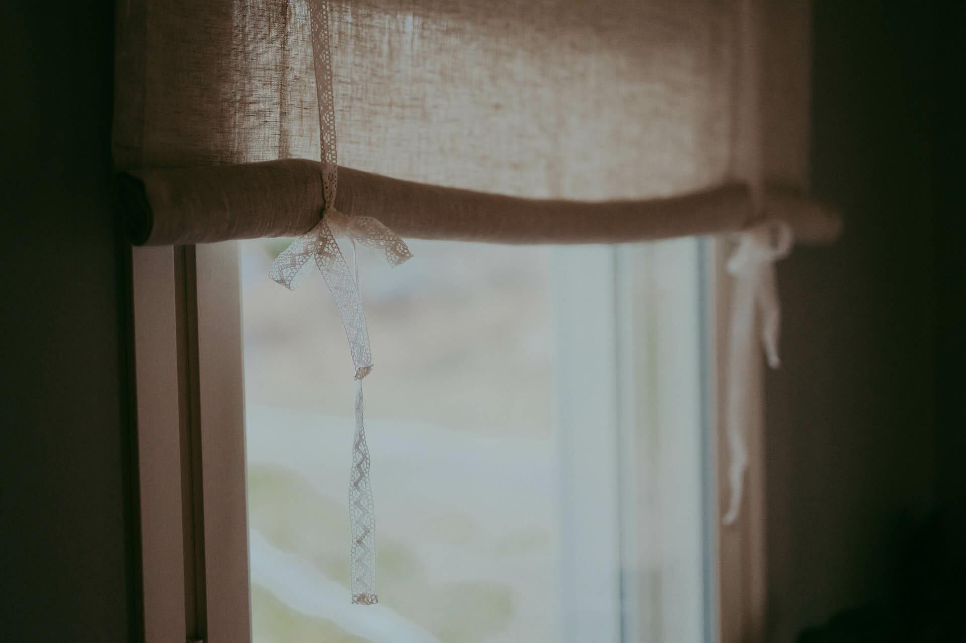 Rullaverhokappa pitsinauhalla ikkunassa.