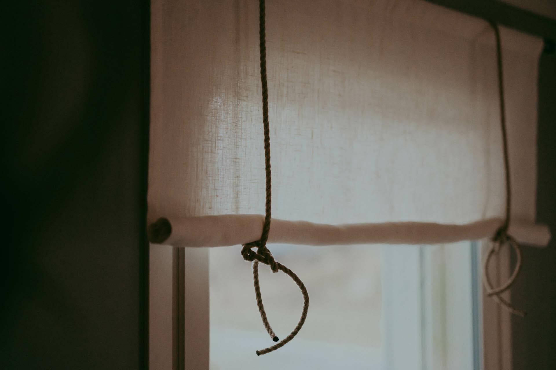 naturvit rullhissgardin med rep i linne hänger i fönster.