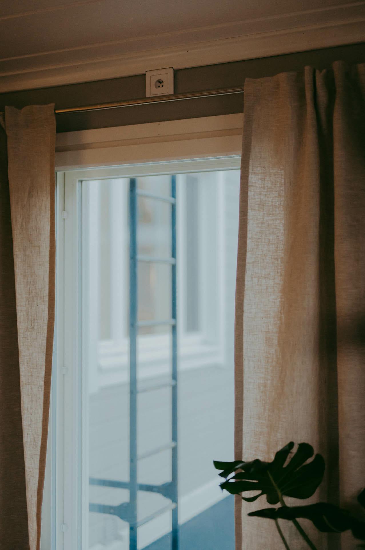 naturvit linnegardin med multiband rynkband hänger på gardinsstång.