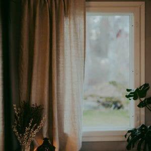 Beiget pellavaverhot ikkunassa.